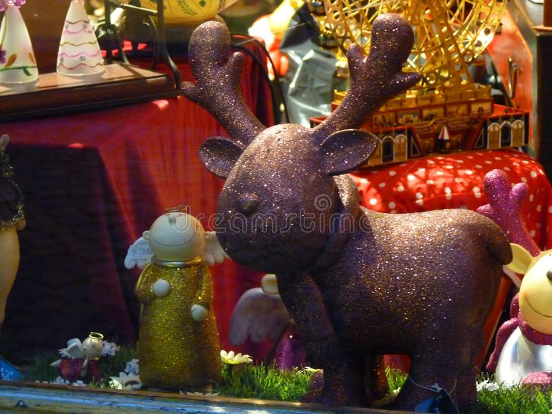 Moose and angel. There is a moose and an angel standing in a shop window royalty free stock images