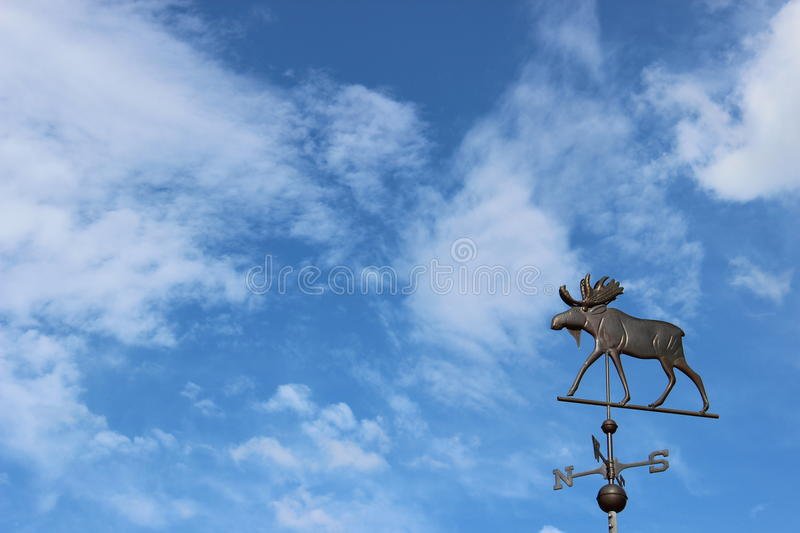 Moose weathervane. Wrought iron weathervane of a bull moose standing against a blue sky with scattered clouds out in rural Maine stock photo