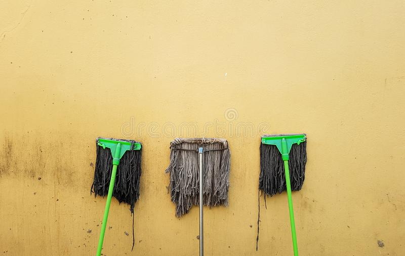 Mop after cleaning on yellow wall stock photography