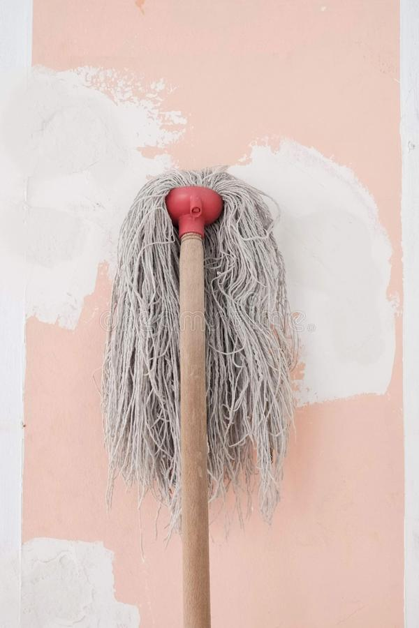 The mop with long cotton gray threads on wooden the stick on the background of the wall pink color with white spots during repair. Mop long cotton gray threads royalty free stock photo