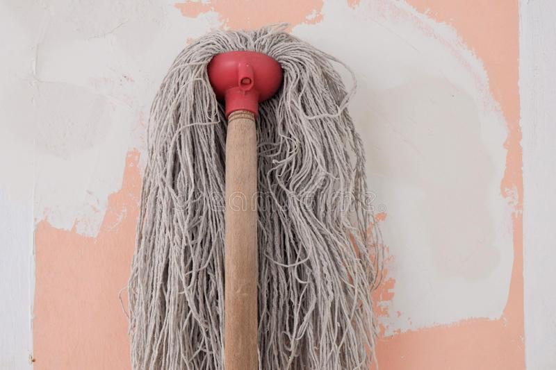 The mop with long cotton gray threads on wooden the stick on the background of the wall pink color with white spots during repair. Mop long cotton gray threads stock photos