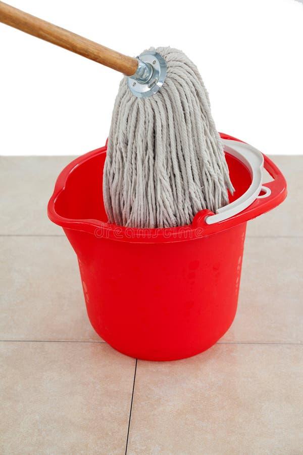 Mop in red bucket on tile floor stock image