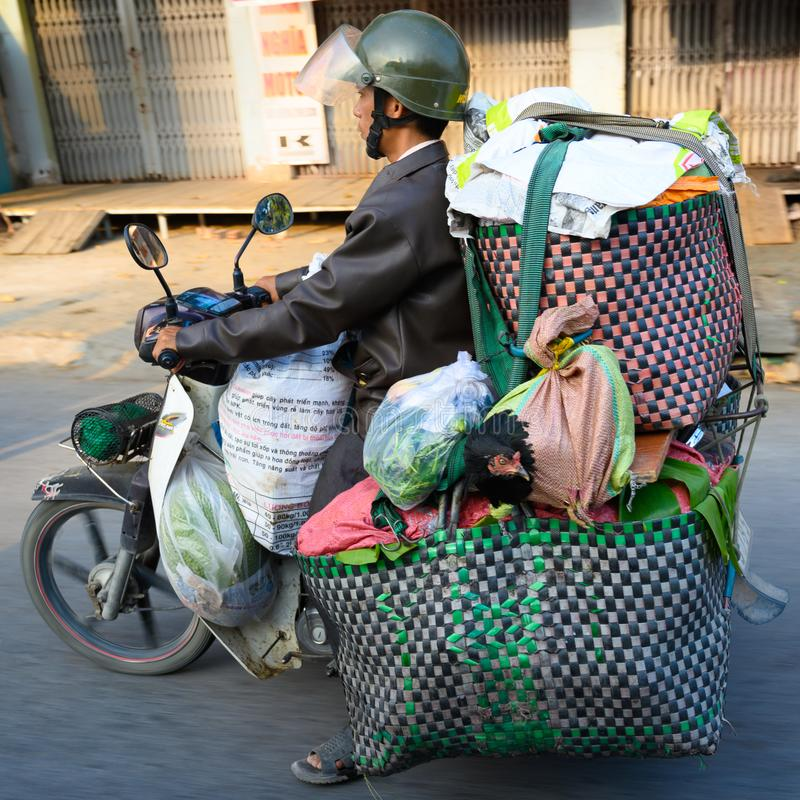 Moped rider Ho Chi Minh City or Saigon, Vietnam. Motorbike driver transporting goods and living hen on motorbike. stock photos