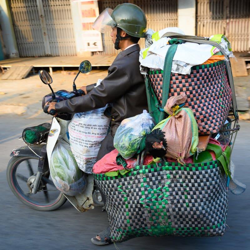 Mopedist Ho Chi Minh City eller Saigon, Vietnam Mopedchaufför som transporterar gods och den bosatta hönan på mopeden arkivfoton