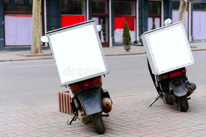 Mopeds service delivery parked on the roadside, rear view. Mopeds parked on the roadside, rear view. Moped service delivery. Pack sign with copy space. Mock-up royalty free stock images