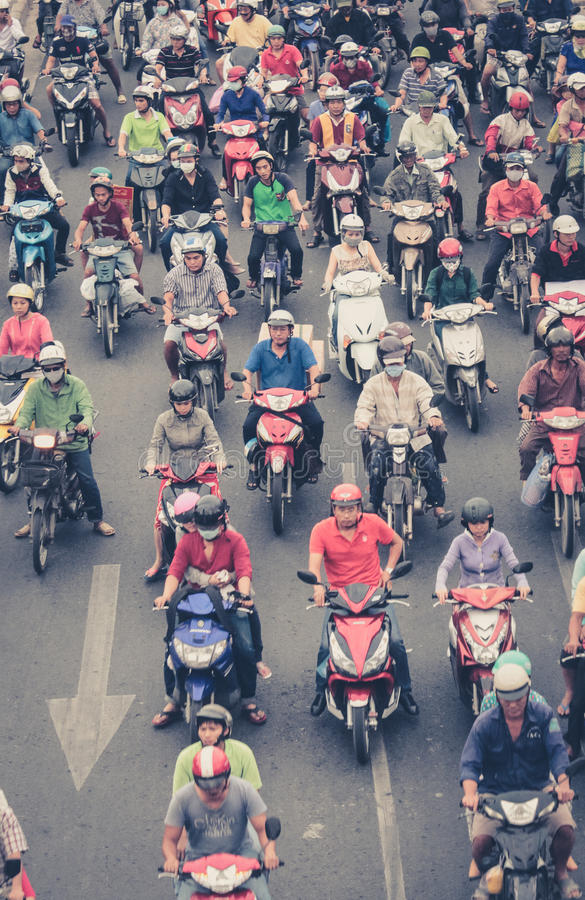 Mopedtrafik i saigon - många sparkcykelchaufförer, fullsatt str royaltyfri bild