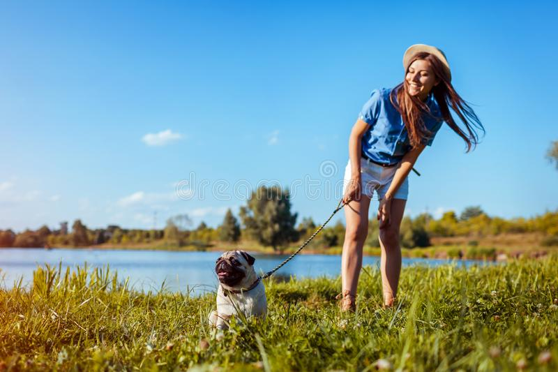 Mopsa psi obsiadanie rzek? Szcz??liwy szczeniak czeka rozkaz mistrz Pies i kobieta chłodzi outdoors fotografia royalty free