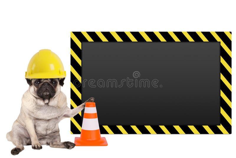 Mopshund med den gula byggnadsarbetaresäkerhetshjälmen och mellanrumsvarningstecknet royaltyfria bilder