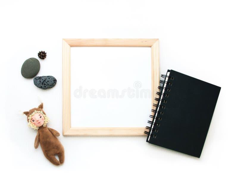 Moquerie étendue plate, vue supérieure, cadre en bois, écureuil de jouet, pierres, bloc-notes noir r photographie stock