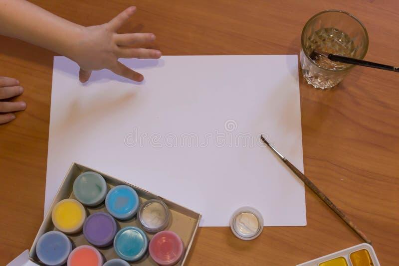 Moquerie blanche de feuille avec des brosses, des peintures acryliques et l'enfant saisissant la main image libre de droits