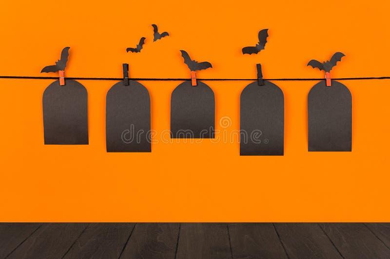 Moquerie d'orange de Halloween vers le haut de fond La vente noire vide marque la tombe accrochant sur des pinces à linge, des ba images libres de droits