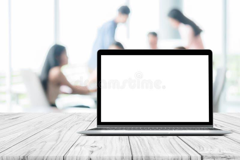 Moquerie de blanc d'ordinateur portable vers le haut de l'écran placé sur la table en bois blanche sur la réunion brouillée de pe image libre de droits