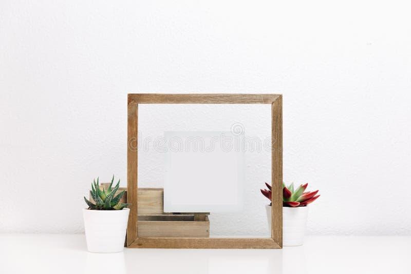 Moquerie de cadre en bois avec des pots de succulents images stock