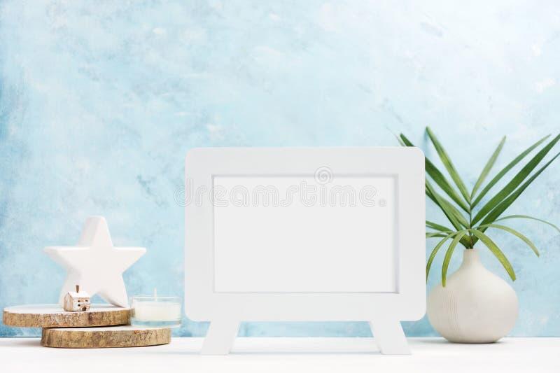 Moquerie de cadre de photo de VWhite avec des usines dans le vase, décor en céramique sur l'étagère sur le fond bleu Type scandin photos libres de droits
