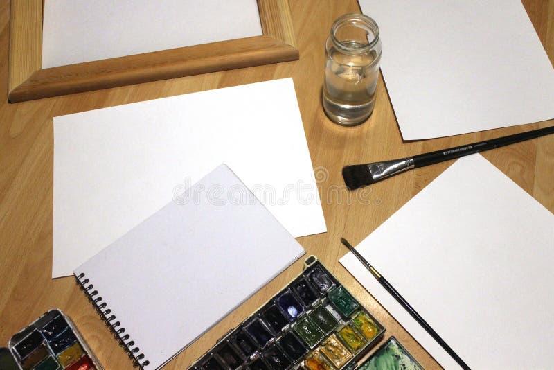 Moquerie de carnet pour l'illustration avec des peintures d'aquarelle, palette, verre de l'eau et pinceaux Outils artistiques de  photo libre de droits