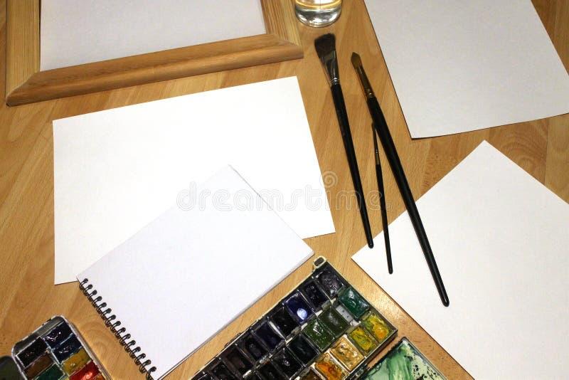 Moquerie de carnet pour l'illustration avec des peintures d'aquarelle, palette, verre de l'eau et pinceaux Outils artistiques de  photographie stock libre de droits