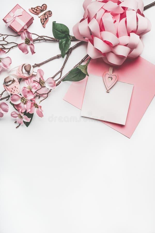 Moquerie de carte de voeux de rose en pastel avec la décoration de fleur, les coeurs, peu de boîte-cadeau et l'arc images stock