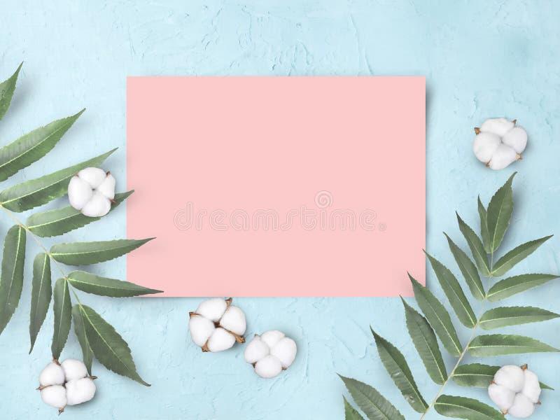 Moquerie vers le haut de blanc de papier rose vide avec des fleurs et des feuilles de coton sur le fond texturisé cyan photographie stock