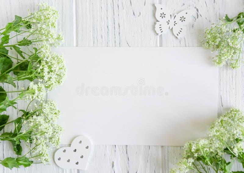 Moquerie vers le haut de papier blanc et d'enveloppe sur le fond en bois fonc? avec les fleurs naturelles de couleur blanche Blan photos libres de droits