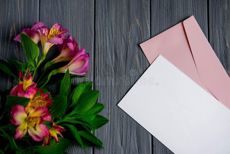 Moquerie vers le haut de papier blanc sur un fond en bois foncé avec les fleurs naturelles de couleur rose Blanc, cadre pour le t photo libre de droits