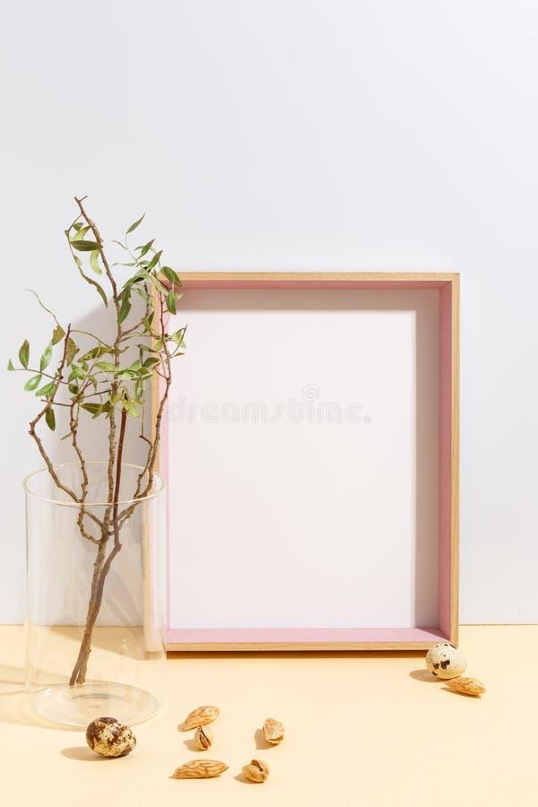 Moquerie vers le haut du cadre blanc et branche avec les feuilles vertes dans le vase bleu sur les ?tag?res ? livres ou le bureau images stock