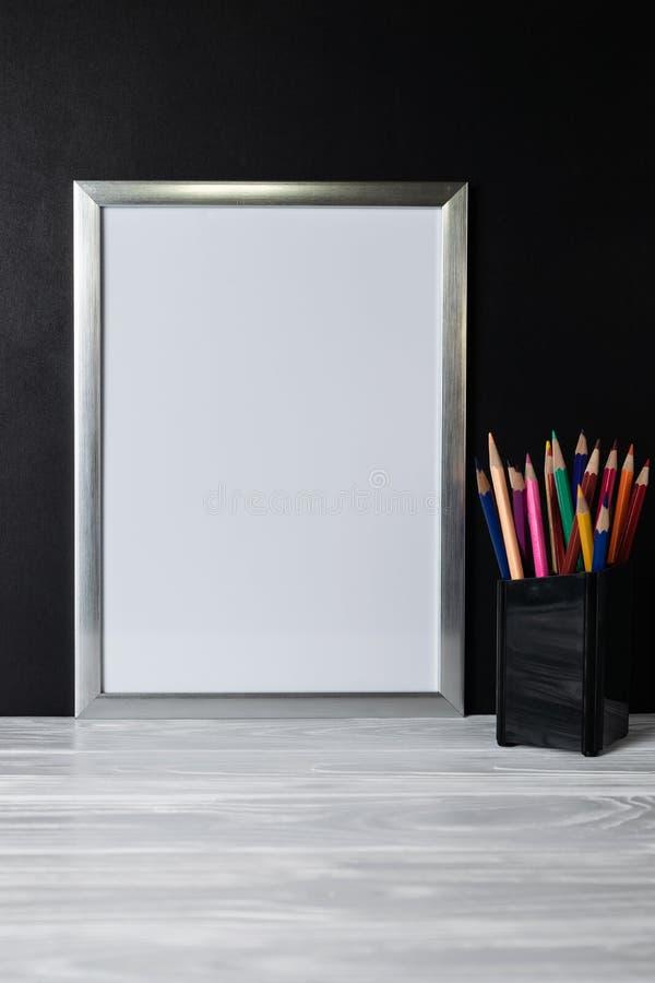 Moquerie vers le haut du cadre blanc et des crayons colorés sur l'étagère et le tableau noir en bois photo libre de droits