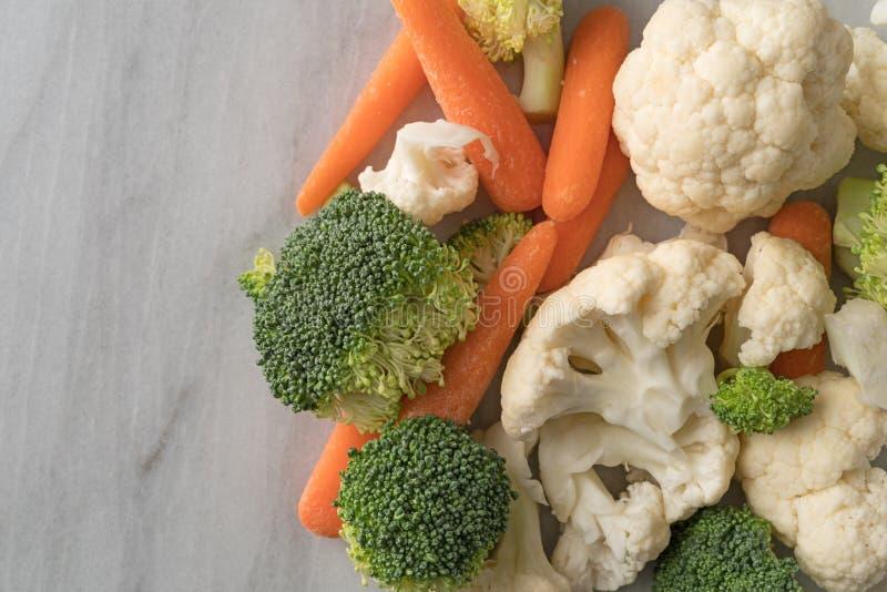 Morötter, broccoli och blomkål på en marmorräknareöverkant arkivbild