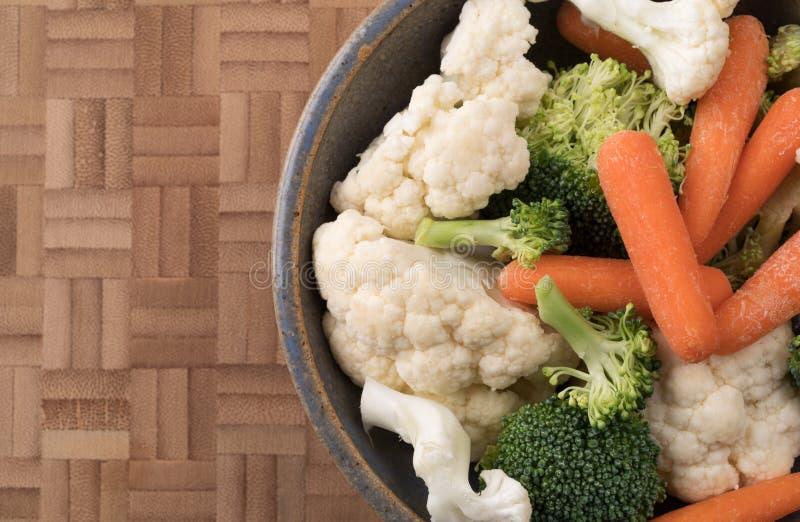 Morötter, broccoli och blomkålen i en stengods bowlar royaltyfria foton