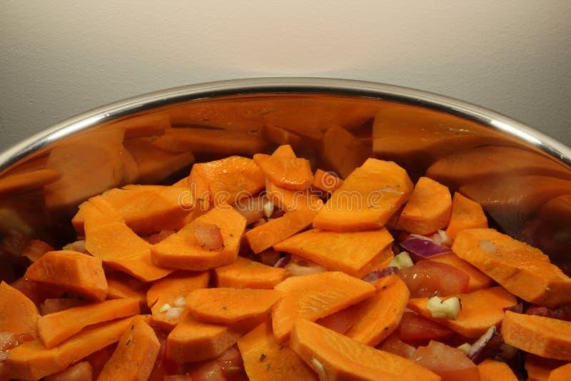 Morötter, tomater, lökar, vitlök och Provencal örter i en panna, innan att laga mat Grönsaker i en kastrull, innan att laga mat royaltyfri bild