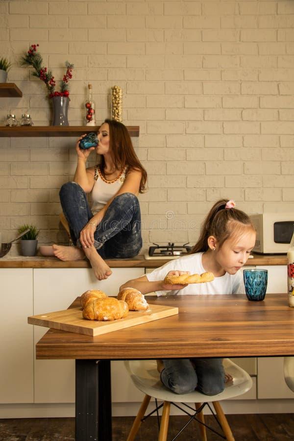 Mor och dotter i köket, äta buntar med mjölk royaltyfri fotografi