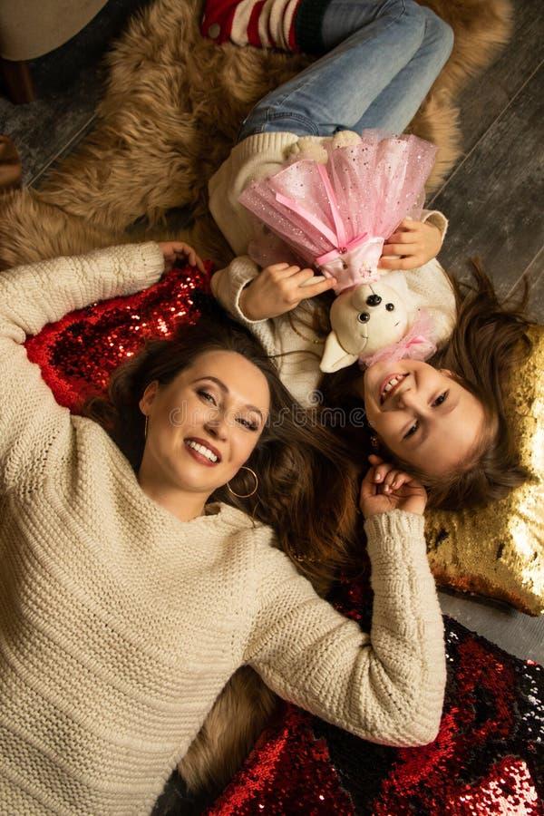 Mor och dotter ligger bland vackra kuddar royaltyfri bild