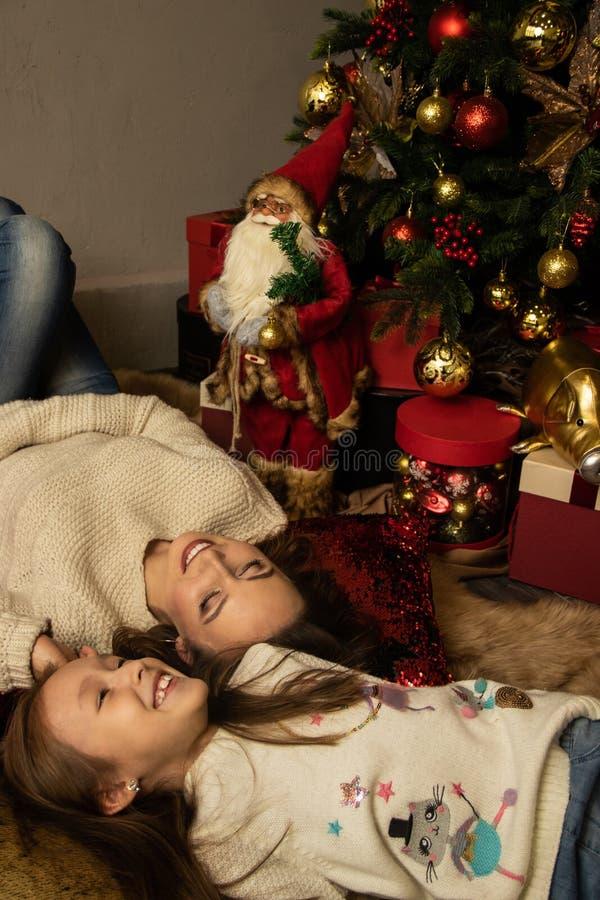 Mor och dotter ligger framför julgranen arkivbild