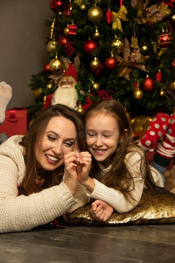 Mor och dotter ligger framför julgranen royaltyfri bild