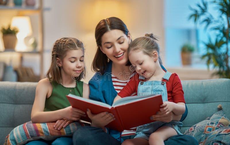 Mor som läser en bok till döttrar arkivbild