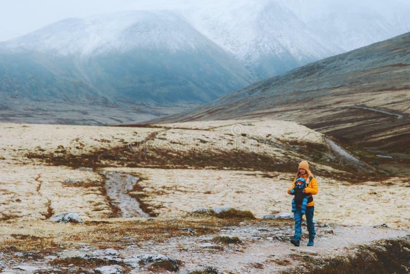 Mor som vandrar med barnbärarfamilj i bergen royaltyfri bild