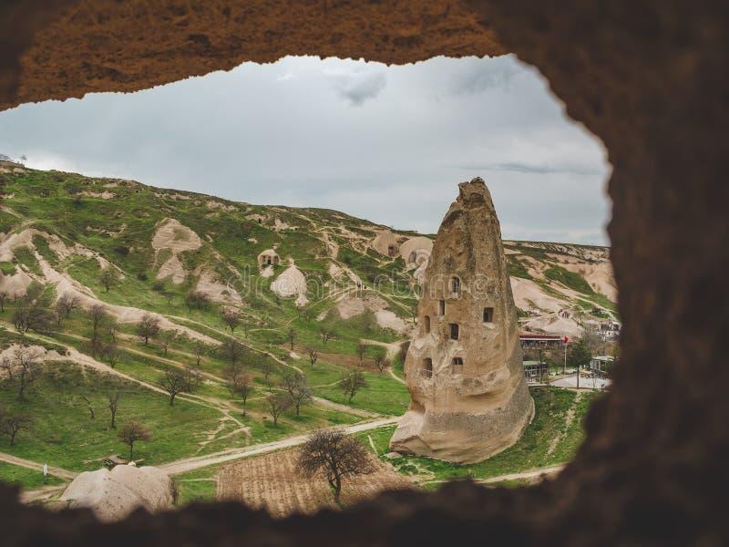 Moradias nas rochas do tufo vulcânico na opinião turca de Cappadocia através do arco de pedra Goreme no inverno frio imagens de stock