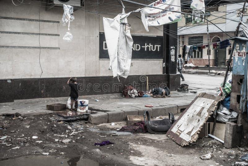 Moradores e vendedores da rua de Nova Deli Menino pobre que banha-se foto de stock