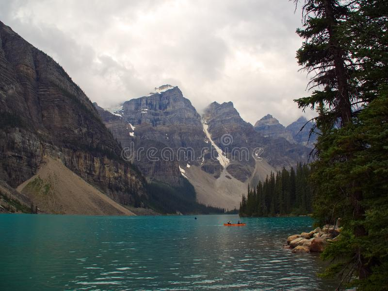 Moraine Lake in Banff National Park Alberta Canada. Moraine Lake on a cloudy, overcast day with dark clouds and turquoise waters of the beautiful lake royalty free stock photography