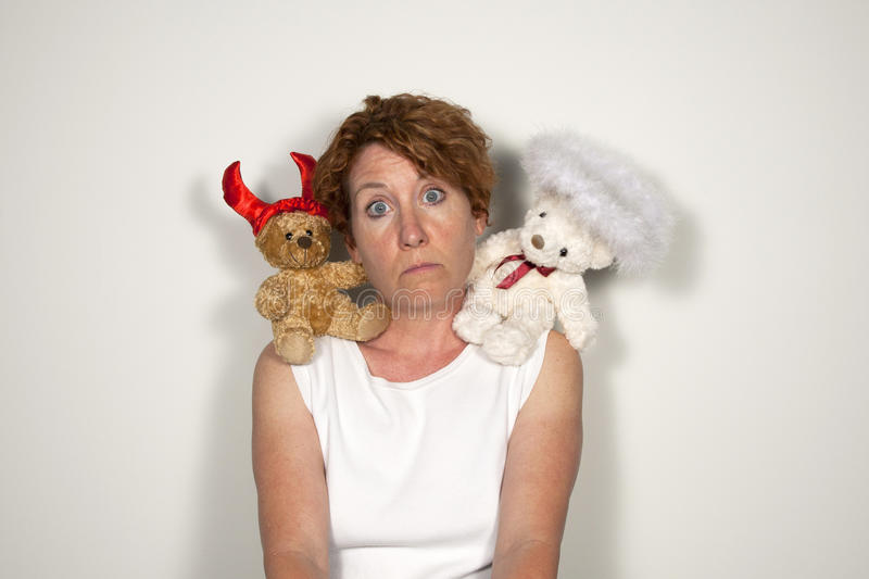 Moral Dilemma. Woman with a Devil bear and an Angel bear on each shoulder looking perplexed stock photography