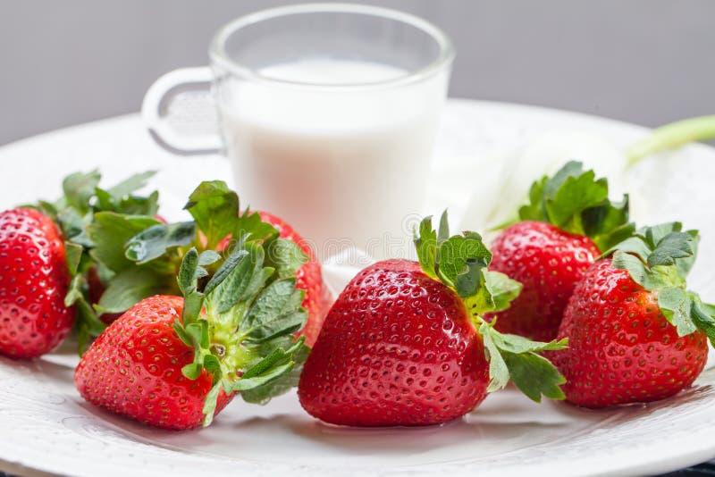 Morango e vidro do leite na placa branca imagem de stock