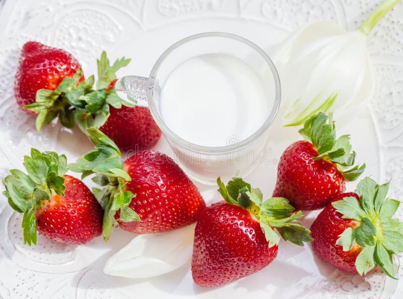 Morango e vidro do leite na placa branca foto de stock royalty free