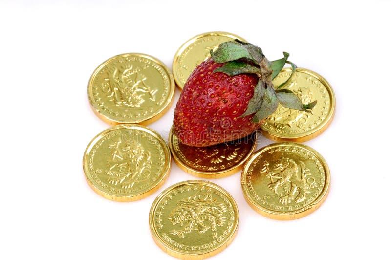Morango em moedas de ouro imagens de stock