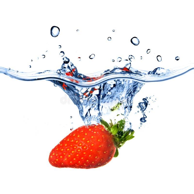 A morango fresca deixou cair na água azul imagens de stock royalty free