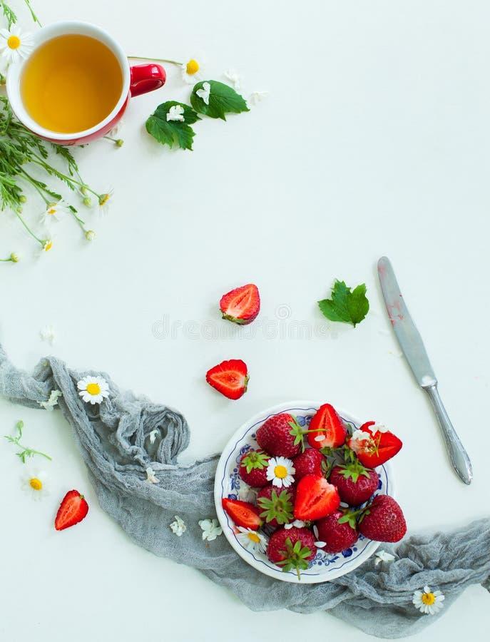 A morango fresca frutifica, as flores, folhas no fundo de madeira branco da tabela fotos de stock royalty free