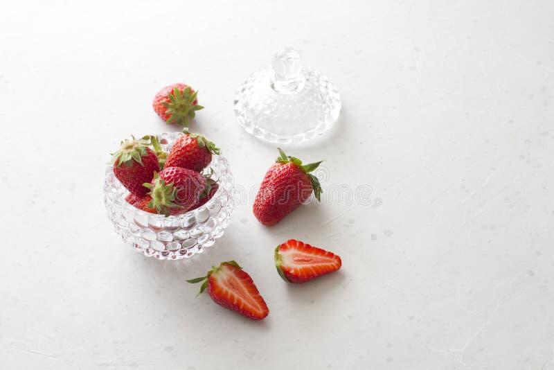Morango vermelha bonita na bacia redonda de vidro Morangos em um fundo concreto branco claro Estilo r?stico Morangos cortadas, imagem de stock