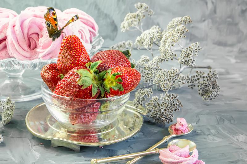 Morango vermelha madura na bacia de vidro com os marshmallows feitos a mão cor-de-rosa no fundo claro bonito Copie o espaço fotos de stock royalty free