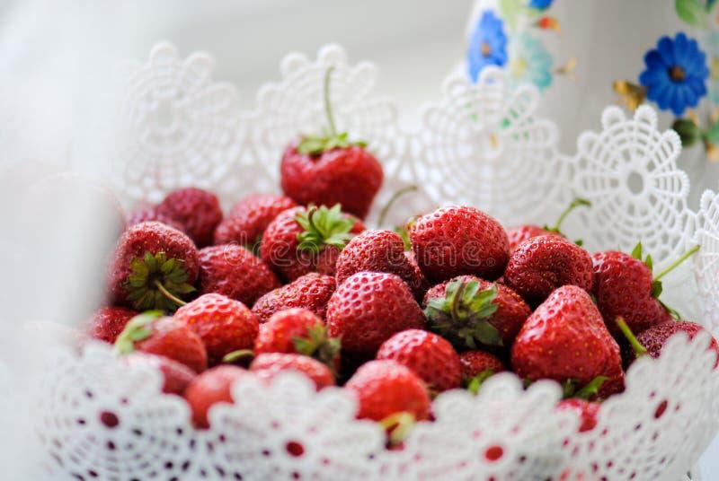 Morangos apetitosas maduras nas bagas de uma cesta branca, do vermelho, as brancas e as verdes, as suculentas fotografia de stock