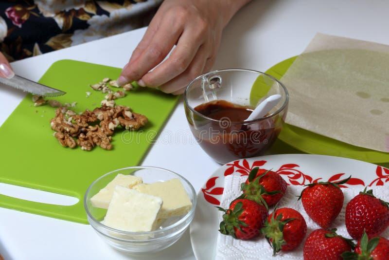 Morangos, chocolate preto e branco Porcas das costeletas da mulher Cozinhar morangos vitrificou no chocolate foto de stock royalty free
