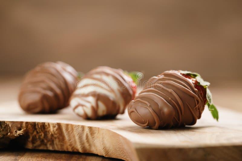 Morangos com cobertura em chocolate na placa de madeira fotos de stock royalty free