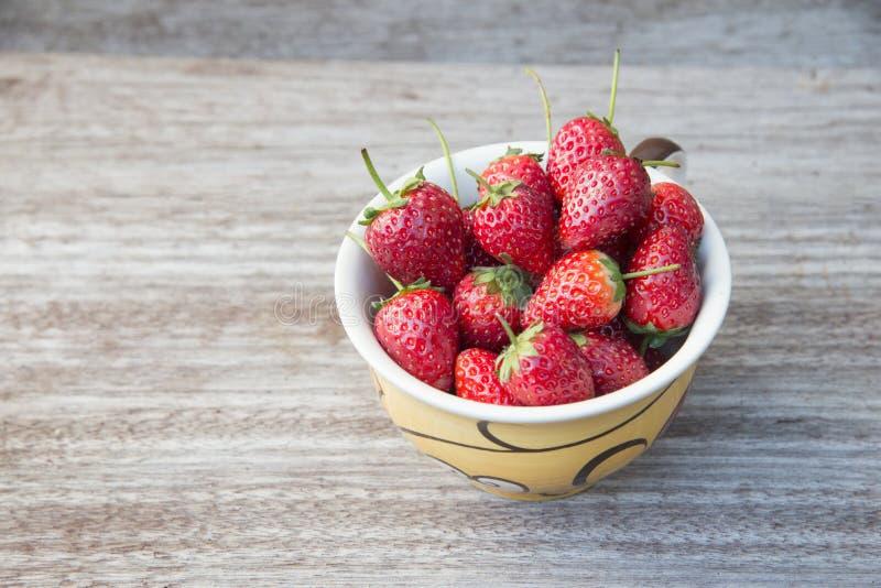 Morangos frescas em uma bacia na tabela de madeira, prepatation strewberry vermelho para fazer o suco da morango Orgânico saudáve imagens de stock